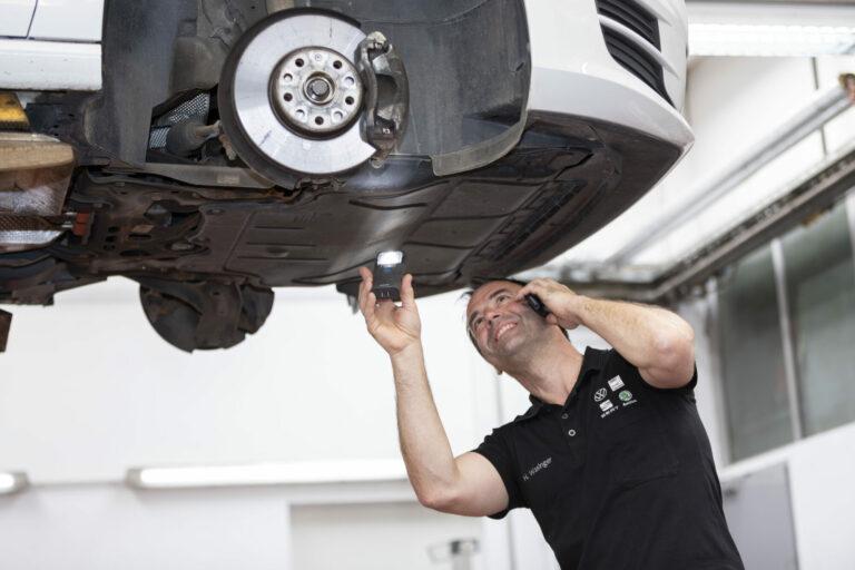 Mann telefoniert in Werkstatt am Auto